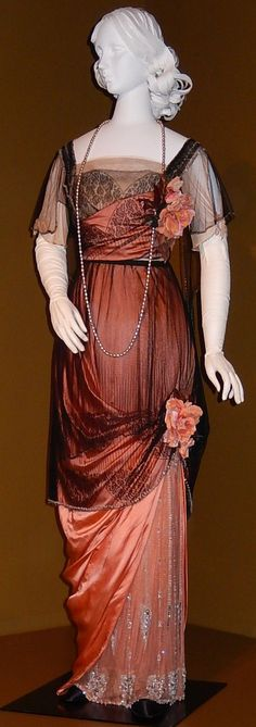 Evening gown, by Jeanne Paquin, France, 1912. Silk satin, netting and lace, glass beads and cotton flowers. Helen Larson Historic Fashion Collection.