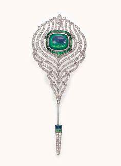 AN ART DECO OPAL AND DIAMOND JABOT PIN   Designed as a openwork single-cut diamond feather, centering upon a bezel-set rectangular cabochon opal within a calibré-cut emerald surround, joined by a single-cut diamond, calibré-cut emerald and sapphire terminal, mounted in platinum and 18k white gold, circa 1925, with French assay mark and maker's mark