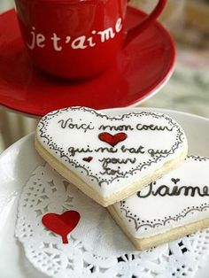"""Valentine's Day in French. Cookies to say I love you. Je t'aime... The top cookie says """"here is my heart that beats only for you"""""""