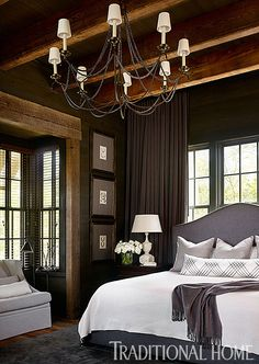 """Bedroom. Master Bedroom Ideas. Classy and rustic master bedroom design. Floor-to-ceiling draperies close behind the camel-backed gray upholstered headboard. Chandelier is the Marigot Eight Light Chandelier from Circa Lighting.  The master bedroom mixes rustic finishes with tailored decor. I love this look!  The bed, a 54-inch-high camel-back upholstered king bed, was custom designed by Douglass Workroom.  Long lumbar pillow on bed  is the """"Valence""""/Dove #11158-01 from Cowtan & Tout.  Bedding..."""
