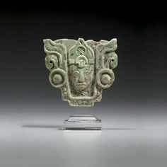 MAYAN JADE PENDANT  LATE CLASSIC, ca. A.D. 550 - 950  boldly carved with the portrait of a dignitary, the rounded face with parted lips, heavy-lidded eyes under thinly arched brows, adorned with large ear flares & a peaked headdress bound by a jade headband & centering a recessed 'kan' emblem, the crossed 'kan' symbol of rulership embellishing the neck, the whole physiognomy sunken within a scrolled cartouche with beadwork lower border; in light green mottled stone...  Height 2 3/4 in.