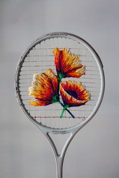 Embroidering rackets rather than swinging them,Danielle Clough (previously) uses thick thread to create multi-colored images of aloe and other fauna on vintage tennis rackets, the strings acting as her loom. Recently the Cape Town-based artist and designer was commissioned by Vans to embroi