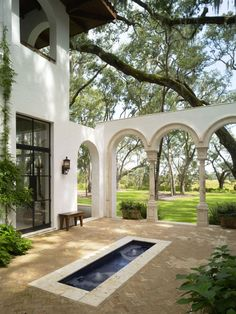 Love the arches leading to the adjacent lawn and the stark contrast of the white stucco and huge live oak.