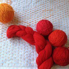 刺し途中のふきん△と赤い糸🍎最近暗めの糸が多かったので明るい糸色で🍊小鳥屋商店さんの新色の赤が気になったので買いました(真ん中かせ)糸玉は上から小鳥屋さん試作糸の紅→no.5→飛騨さしこさんの糸no.41 です。赤も色々〜❤️#刺し子#sashiko#花ふきん#sashikostitching#stitching#handstitched#刺し子糸 #小鳥屋商店 #飛騨さしこ