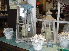 by the shore...rustic lanterns and potted shells  www.swansfurniture.com