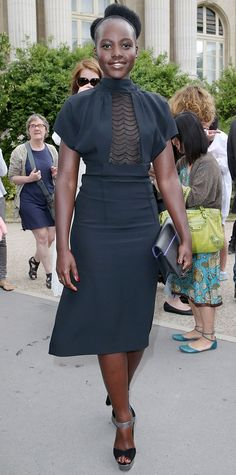 Lupita Nyong'o continued to hit the couture circuit, stopping by the Maison Martin Margiela fall 2015 show in a cape-sleeved lace-paneled LBD, complete with gunmetal accessories.