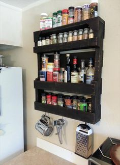 Isn't it amazing that a coat of black paint takes an average pallet from rustic to sleek almost immediately? Even better: This wooden shelving unit features four shelves for spices — not to mention hangers for a cheese grater and more below. See more at Pallet Furniture DIY »  - GoodHousekeeping.com