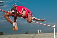 African American male High jumper clearing the high jump bar, athletic track event - Ty Allison/Photographer's Choice/Getty Images