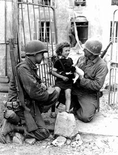 Two GIs are trying to comfort a little French girl who found herself in the middle of the fighting in her unidentified town. One of the GIs has enlisted the help of a puppy. Humanity in the middle of horrendous devastation, fall 1944.