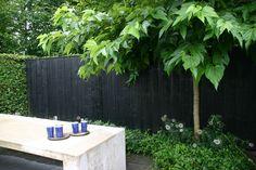 Schutting achterin de tuin van zwarte rabat delen? Horizontale planken.