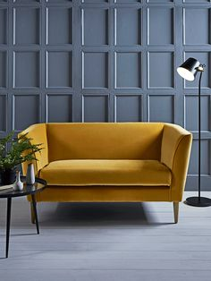 Handmade in the UK with a solid birch and beech hardwood frame, our high quality occasional sofa has a luxurious mustard yellow cotton velvet finish and four slender solid oak legs. Simple in shape with a fixed cosy seat cushion, sprung back and cushioned armrests, each piece is padded with high density foam, which has been interwoven by hand with a feather wrap and elasticated webbing. Beautiful in its versatility, our statement Timsbury Sofa can be styled to suit your home.