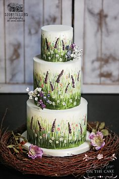 Hand painted pretty summer meadow scene wedding cake with wild flowers and grass and lavender. This unique design is perfect for an outdoor country wedding, would also be a lovely  for a Woodland theme or Boho festival wedding.