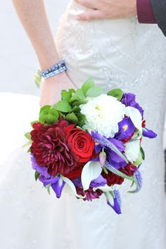 White calla lilies, white and burgundy dahlias, red roses, and purple lisianthus, iris, and veronica give this wedding bouquet by Jasmine's Garden beautiful texture.