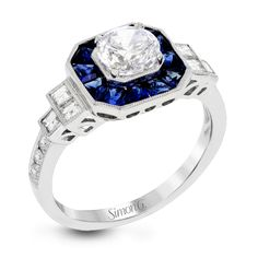 This 18k white gold engagement setting would be a perfect 'something blue' with .79 ctw of baguette sapphires in a halo surrounding the center stone. These are framed by .33 ctw of princess cut diamonds and .11 ctw of round brilliant diamonds.