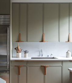 "Wood cabinet pulls designed by NYC-based firm Workstead, and cabinets painted ""french gray"" by Farrow & Ball"