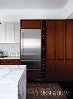 An elegant wine rack delineates the space between the fridge and pantry. | Design: Suzanne Dimma and Arriz Hassam | Photo: Angus Fergusson