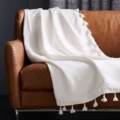 Shop Linen White Throw with Tassels. Soft dobby weave covers sofa/accent chair/you in a lightweight, cozy layer. Simple linen throw in pure white is finished luxe with cotton tassels on all four sides.