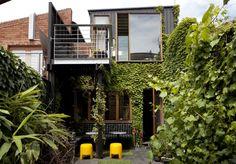 Amanda Lynn's beautiful urban backyard retreat. Climbing plants, yellow stools and modern architecture.
