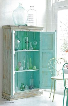 A teal inspired collection of coloured glass beautifully displayed.