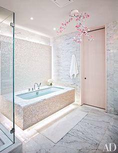 The wife's bath in a Manhattan penthouse by ODA-Architecture is accented with a chandelier by Studio Tord Boontje for Swarovski and custom-made mother-of-pearl mosaic tiles; the tub is by Duravit, with fittings by Fantini | archdigest.com