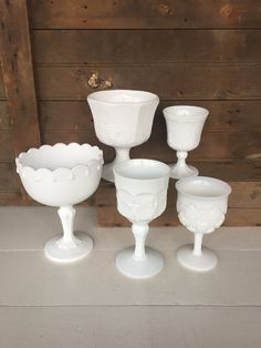 Here is a collection of 5 milk glass compotes. These are all opaque milk glass and have that deep white color. In good condition with no chips or cracks. There are some scuffs inside and watermarks (see photo #3). This collection makes a beautiful centerpiece grouped together. A great cottage chic look. Thanks for looking! Please look over photos carefully. Any questions, please contact me.  Left to Right (photo #2) -  Plain with Tear Drop - 7 1/2 high and 5 1/2 across the top  Thum...