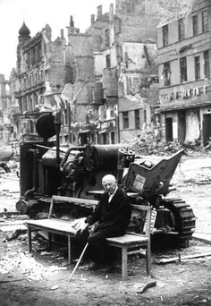 An elderly man sits alone among the ruins after the Battle of Berlin (May 1945).