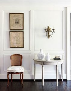 foyer, black floors, white walls, molding