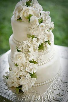 White wedding cake with beautiful cascading sugar flowers.