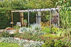 Pergolan är byggd som en luftig skiljevägg, från husknuten till häcken vid tomtgränsen. I förgrunden, kantsatta och upphöjda odlingsbäddar för jordgubbar, smultron och rabarber. Grusgårdens terrakottakärl är fyllda med fetbladsväxter och stenar.