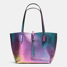 Pebble leather with a striking iridescent finish gives this minimalist tote subversive shimmer and an unexpected downtown edge. The spacious silhouette has long, slender handles for easy wear and a strap secured by a diminutive Coach turnlock.