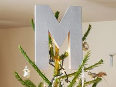 HGTV Tree Topper  Put your personal stamp on the tree with a monogram topper. Spray-paint a 12-inch papier-mache letter (available in craft stores) with Glitter Blast spray paint in Silver Flash by Krylon for a sparkly homemade initial.