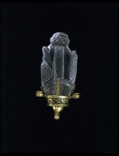 Made of rock crystal, this pendant is in the form of a fish. It has a fin at the top, carved with diaper work, and two carved fins below. The body ends in a stylised tail and a deep tube is pierced down its middle. The crystal probably dates from the Fatimid period (AD 969-1171), and was perhaps carved by an Islamic craftsman in Cairo.