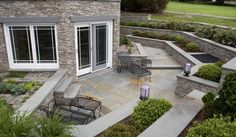 stone patio with stacked stone exterior, white window trimmings, and wrought iron patio furniture.