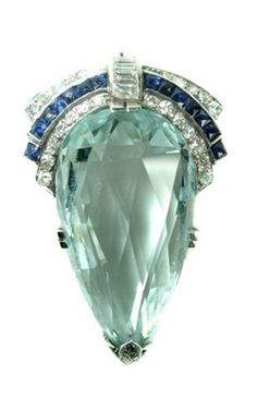 This 1930s brooch is a superb example of Art Deco design, has a large 35.10ct briolette cut aquamarine,light sky blue in colour and set in 18kt. The  twenty-four single cut and four baguette cut diamonds, and fourteen calibre cut synthetic sapphires, set off the colour and cut of the aquamarine..  Total weight of the diamonds is 0.50ct