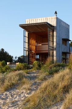 """Tiny two stories holiday retreat on a sandy beach in New Zealand, design by Crosson Clarke Carnachan Architects. The """"roofs"""" over the windows can all be lowered to close up the cabin when not in use. Due to coastal erosion the cabin is also on a sled so it can be moved if needed."""