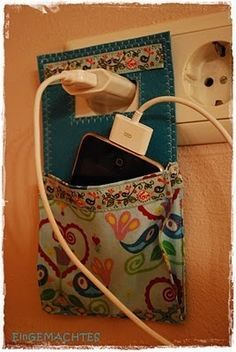 This out of two jean pockets back to back, with a ribbon ow wire loop to hang from the plug. Use the back pocket to loop the extra cord and the front pocket to hold the phone!