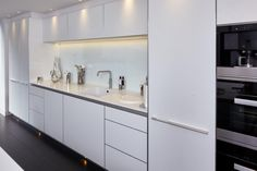 bulthaup b3 kitchen in Alpine White laminate with a Natural Aluminium island. Miele and Gaggenau appliances. Corian worktops from Counter Production