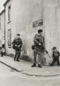 A little boy walking to his friends encounters British soldiers around the corner in Belfast, Northern Ireland. 1973