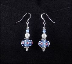 Adorable earrings. Blue, pink, and white lampwork glass bead earrings.   *Beads: Lampwork and glass beads   *Earwires: Sterling silver   *All other metal is silver plated.   *Length: 1.6 inches (from the bottom of the ear hook)   *Width: 0.65 inches (at the widest part)   *Handcrafted in Fayetteville, Arkansas
