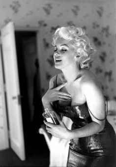 Ed Feingersh ~ Marilyn in her New York hotel suite putting the finishing touches to her  evening attire with a touch of Chanel No. 5, 1955