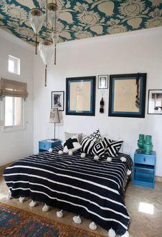une chambre à coucher ethnique chic aux accents déco marocains, couverture rayée marocaine à pompons associée à des coussins motif géométrique