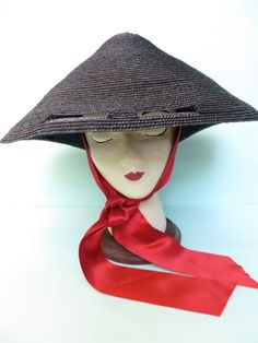 This retro style black straw sun hat by British hat designer Lucy Barlow will definitely keep you in the shade. High quality construction. Ms. Barlow specializes in straw called Italian Paglina Braid and works with the old stitch straw machines to make her hats. This gives them an authentic retro feel. Large cone shape has eye cut outs and a wide red silk satin ribbon that ties at the chin. Interior of the hat has a mini hat that secures it to the crown of the head and is trimmed with…