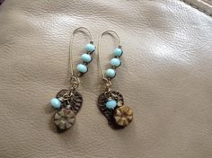 Wire wrapped ammonite beads on French ear wires , with brass accents and Czech glass flowers .