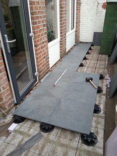Een bestaand dakterras met betontegels is vernieuwd door de toepassing van 2 cm keramische tegels, die gedragen worden door verste...