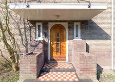 Jaren30woningen.nl | Stijlvolle entree met grote luifel, rood wit stoepje en klassieke voordeur