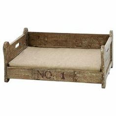 """Weathered wood pet bed with a cushion.   Product: Pet bedConstruction Material: Wood and fabricColor: Vintage brownFeatures: Cushion includedDimensions: 12"""" H x 28"""" W x 22"""" D"""