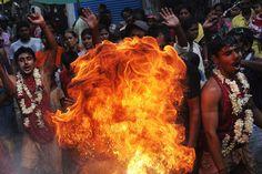Kolkata, Indien, 12. April 2012:  Hindu-Anhänger werfen bei einer Zeremonie während des Gajan-Festivals in Kolkata zu Ehren der Geburt Shivas, einer der wichtigsten Gottheiten im Hinduismus, brennbares Pulver in ein Feuer.