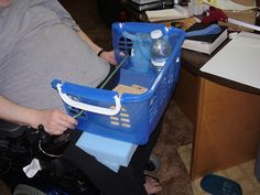 Adapted basket used as carrying tray for power wheelchair, with cutaway front for access and bungee cord to hold it on the chair.  Foam wedge underneath was needed to level the basket.  Outreach Therapy Consultants
