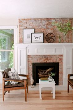 Exposed brick fireplace with white painted mouldings and light wood floor.