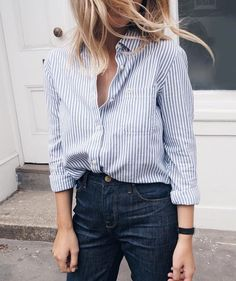 Light striped button-up top tucked into navy blues.